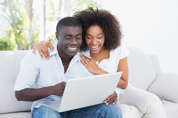 Atrakcyjna para używa laptop wpólnie na kanapie