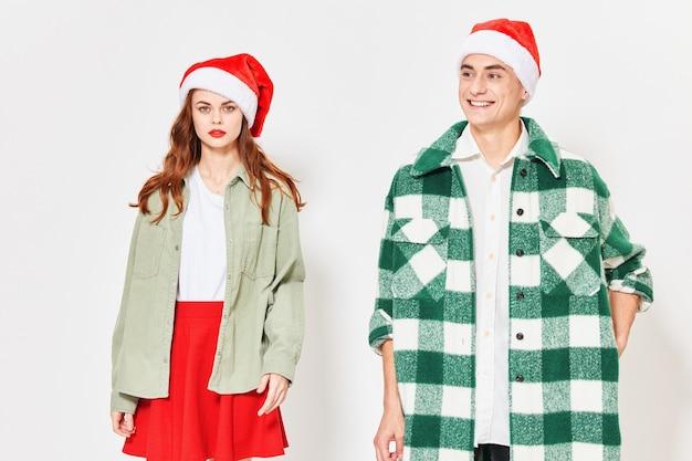 Atrakcyjna para w świąteczne czapki na jasnym tle przycięty widok. wysokiej jakości zdjęcie