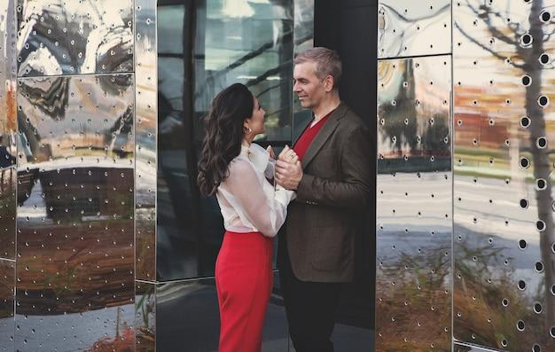 Atrakcyjna para współpracowników rozmawiających i flirtujących w pobliżu biura biznesowego mężczyzna i kobieta randki
