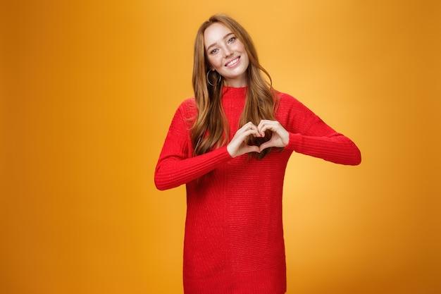 Atrakcyjna, pewna siebie i urocza dziewczyna imbir z piegami w czerwonej, ciepłej sukience z dzianiny, pokazując gest miłości, przechylając głowę i uśmiechając się szeroko do aparatu, upodobanie i adorowanie nowego stroju na pomarańczowym tle