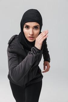 Atrakcyjna, pewna siebie młoda muzułmanka nosząca sportowy hidżab biegający na białym tle