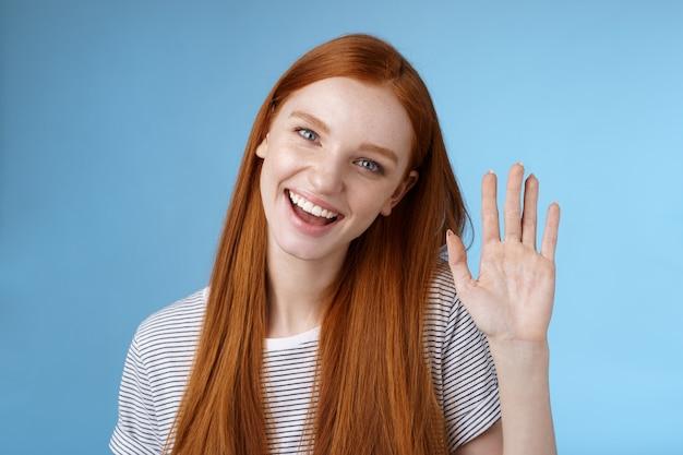 Atrakcyjna pewna siebie ruda sassy dziewczyna czysta czysta skóra niebieskie oczy przechylająca głowę radośnie machająca ręką cześć cześć gest powitanie wyglądasz przyjazny aparatowi powitanie przyjaciela, stojącego w tle studia.
