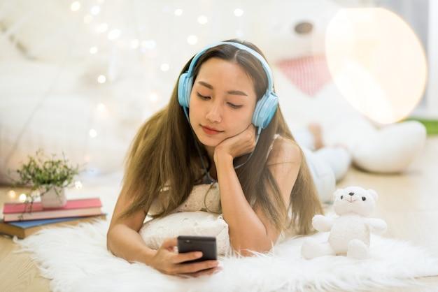 Atrakcyjna piękna azjatycka młoda kobieta gra w mediach społecznościowych i słucha strumieniowej muzyki online za pomocą smartfona i słuchawek w salonie z pierwszym planem światła bokeh. relaks w weekend.
