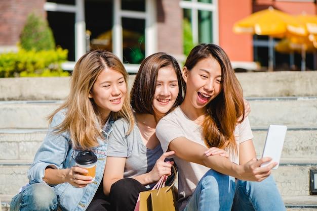 Atrakcyjna piękna azjatykcia kobieta używa smartphone podczas gdy robiący zakupy w mieście
