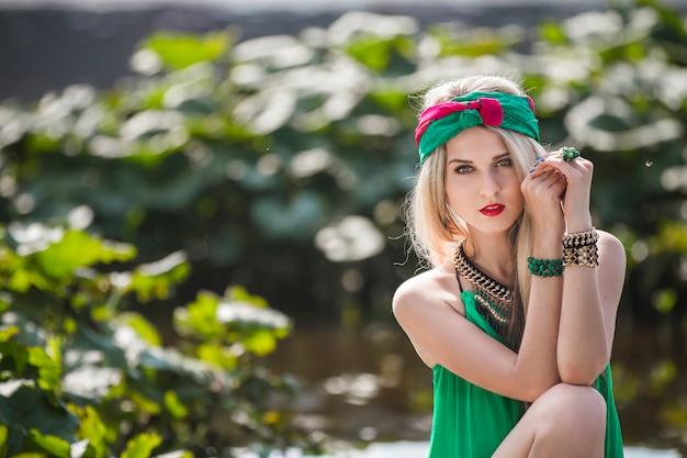 Atrakcyjna piękna blondynka w szortach i opasce chodzi i pozuje w parku