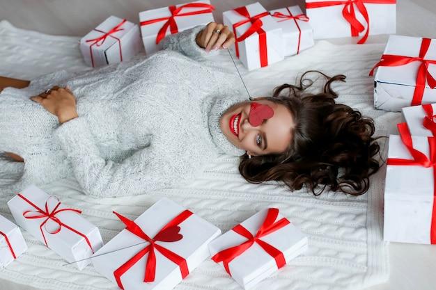 Atrakcyjna piękna i seksowna kobieta z doskonałym uśmiechem i zębami. z makijażem na urodziny lub walentynki z prezentem i balonami