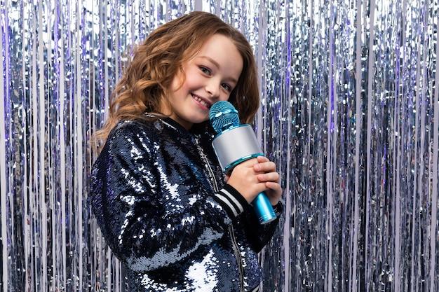 Atrakcyjna piękna młoda dziewczyna kaukaski prowadzi z mikrofonem na tle świecidełka.