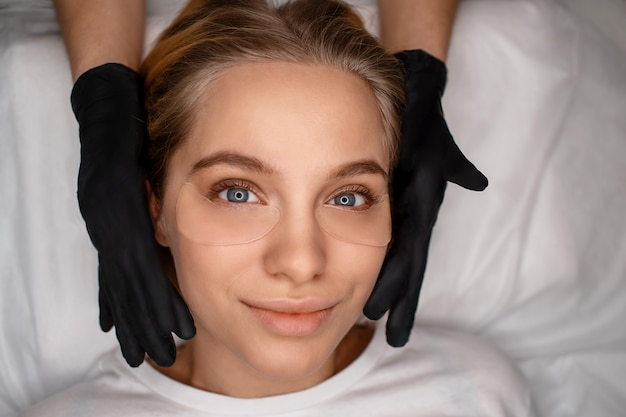 Atrakcyjna piękna młoda kobieta, leżąc i patrząc prosto. ona jest przekonana. kosmetyczka dotyka twarzy dłońmi w czarnych lateksowych rękawiczkach.