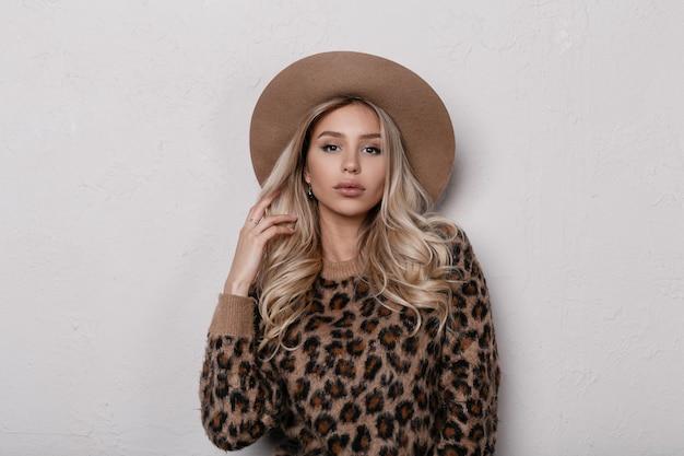 Atrakcyjna piękna młoda kobieta w eleganckim beżowym kapeluszu w modnym swetrze lamparta z kręconymi blond włosami z naturalnym makijażem i seksownymi ustami