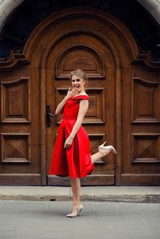 Atrakcyjna piękna szczęśliwa kobieta w czerwonej sukience z doskonałym uśmiechem zasłaniającym usta jedną ręką i stoi na jednej nodze nad starymi zabytkowymi drewnianymi drzwiami