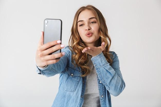 Atrakcyjna podekscytowana młoda dziewczyna stojąca na białym tle nad białym, biorąca selfie, wysyłająca buziaka