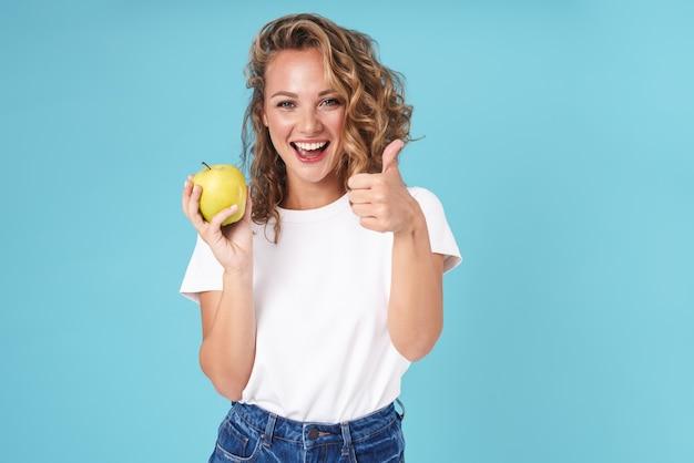Atrakcyjna podekscytowana młoda dziewczyna ubrana w zwykłe ubranie, stojąca na białym tle na niebiesko, pokazując jabłko i dając kciuk w górę