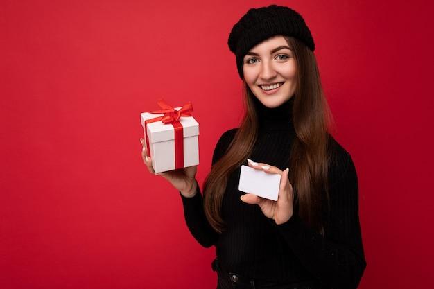 Atrakcyjna pozytywna dorosła brunet kobieta ubrana w czarny sweter i kapelusz odizolowane na czerwono