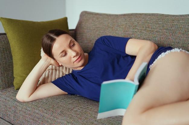 Atrakcyjna pozytywna kobieta czyta książkę relaksuje na kanapie