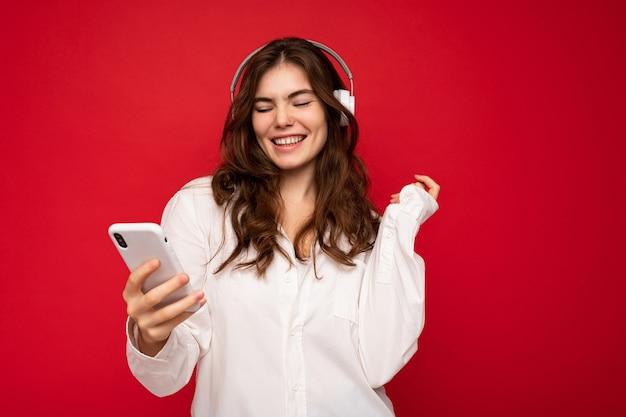 Atrakcyjna pozytywna młoda brunetka kręcone kobieta ubrana w białą koszulę odizolowaną na czerwonym tle ściany