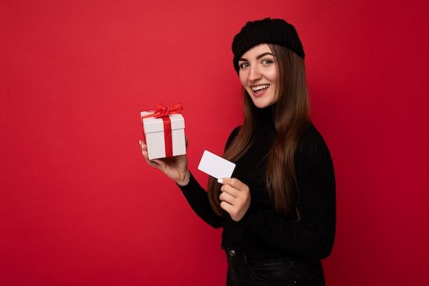 Atrakcyjna pozytywna młoda brunetka ubrana w czarny sweter i kapelusz odizolowane na czerwono