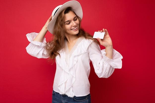 Atrakcyjna pozytywna uśmiechnięta młoda ciemna blondynka ubrana w białą bluzkę i biały kapelusz na białym tle na czerwonym tle trzymając kartę kredytową patrząc na zbliżeniową kartę plastikową.