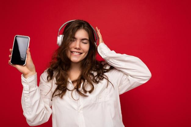 Atrakcyjna pozytywna uśmiechnięta młoda kobieta ubrana w stylowy strój dorywczo na białym tle na kolorowy