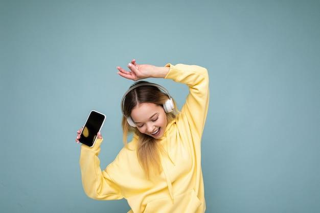 Atrakcyjna pozytywna uśmiechnięta młoda kobieta ubrana w stylowy, swobodny strój na kolorowym tle