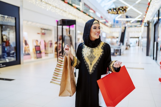 Atrakcyjna pozytywna uśmiechnięta muzułmanka w tradycyjnym stroju, chodząca w centrum handlowym z torbami na zakupy w rękach i szukająca innego prezentu dla bliskich.