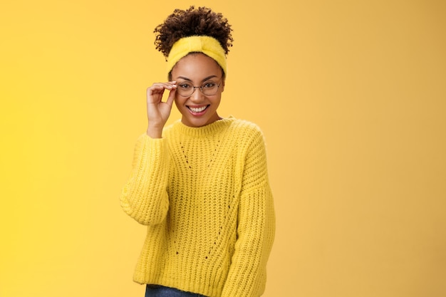 Atrakcyjna przyjazna charyzmatyczna programistka frontend developer uśmiechnięta szeroko okulary nos wygląda pewnie szczęśliwa ma świetny pomysł na poprawę funkcjonalności aplikacji, stojąc na żółtym tle.