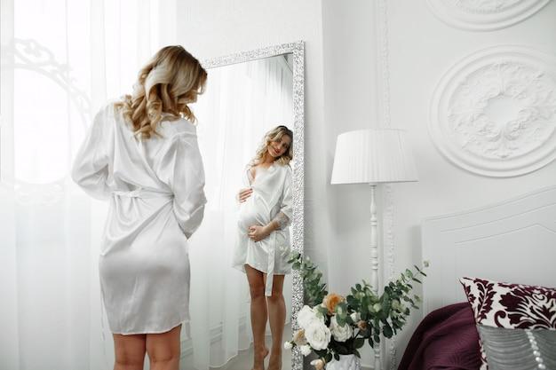 Atrakcyjna przyszła mama w bieliźnie w sypialni przed lustrem. szczęśliwa kobieta w ciąży czule głaszcze brzuch pod lustrem