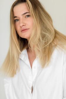 Atrakcyjna pulchna dziewczyna pozuje w białej koszuli, pozytywna koncepcja wysokiej jakości zdjęcia