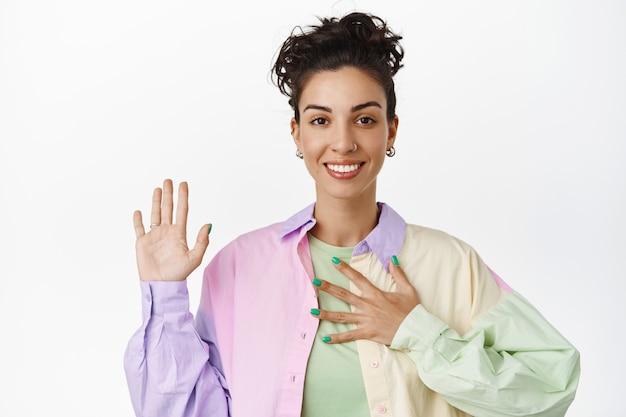 Atrakcyjna queerowa dziewczyna podnosząca rękę, trzymająca rękę na piersi, przedstawiająca się, zgłaszająca się na ochotnika, składająca obietnice, stojąca na białym