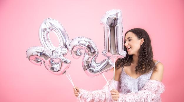 Atrakcyjna radosna dziewczyna na różowym tle ze srebrnymi balonami na nowy rok w dłoniach