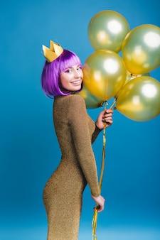 Atrakcyjna radosna młoda kobieta w luksusowej modnej sukni świętuje wielką imprezę. złote balony, korona, obcięte fioletowe włosy, jasny makijaż, uśmiechnięty, święta.