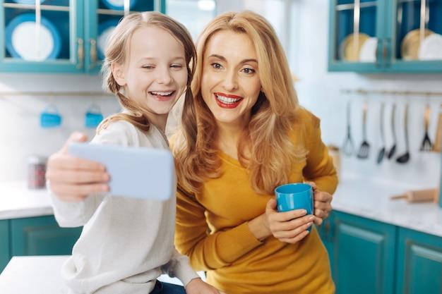 Atrakcyjna, radosna, szczupła jasnowłosa matka uśmiecha się i trzyma filiżankę herbaty, podczas gdy jej córka robi selfie