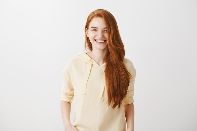 Atrakcyjna ruda kobieta uśmiecha się z białymi zębami, czuje się szczęśliwa