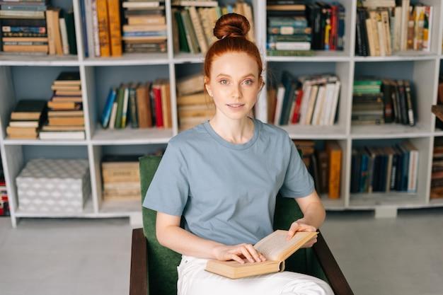 Atrakcyjna ruda młoda studentka czyta książkę lubi odpoczywać w domu, patrząc na kamerę