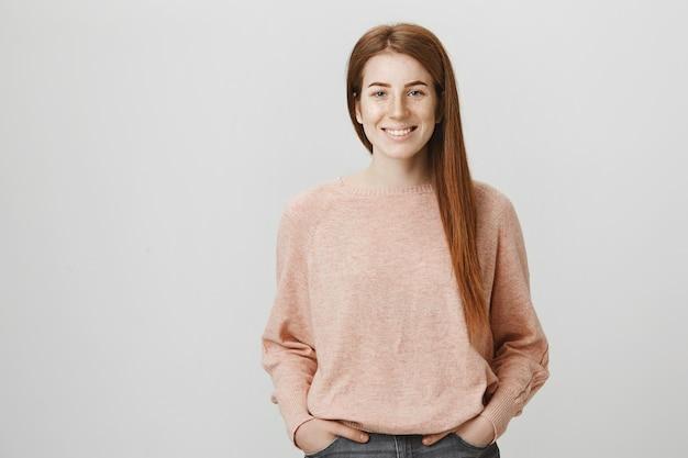 Atrakcyjna ruda studentka uśmiechnięta szeroko