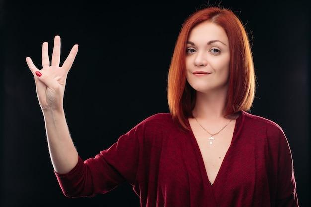 Atrakcyjna rudowłosa dziewczyna trzyma rękę z 4 palcami w górę.