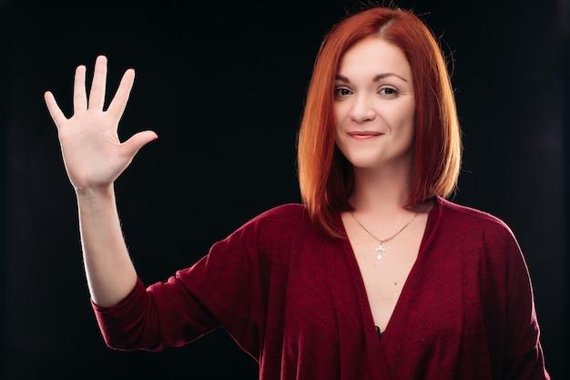 Atrakcyjna rudowłosa dziewczyna trzyma rękę z 5 palcami w górę.