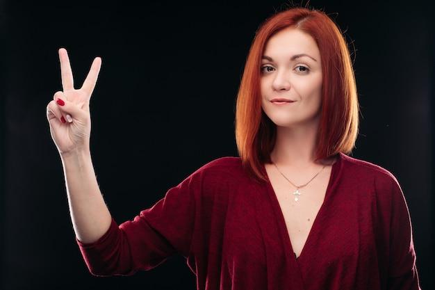 Atrakcyjna rudowłosa dziewczyna trzyma rękę z dwoma palcami w górę.