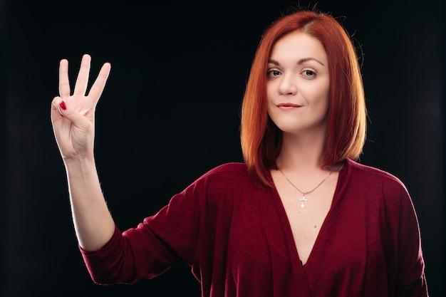 Atrakcyjna rudowłosa dziewczyna trzyma rękę z trzema palcami w górę.