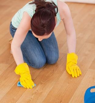 Atrakcyjna rudowłosa kobieta czyszczenia podłogi podczas klęczenia