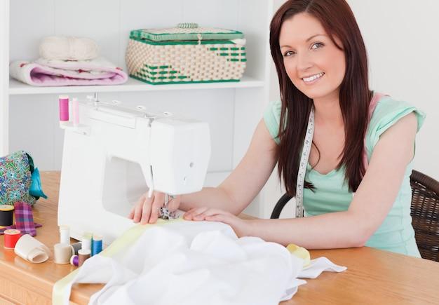 Atrakcyjna rudowłosa kobieta za pomocą maszyny do szycia w salonie