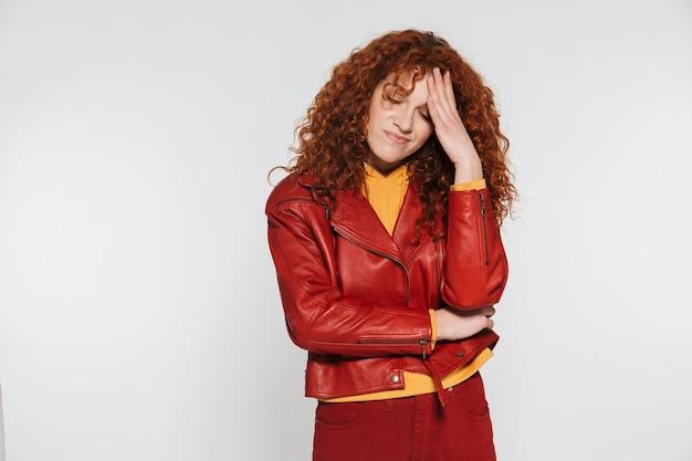 Atrakcyjna rudowłosa młoda kobieta stojąca odizolowana, mająca migrenę