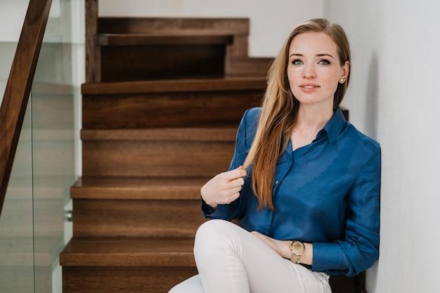 Atrakcyjna rudowłosa młoda kobieta ubrana w niebieską koszulę i białe spodnie siedząca na schodach w jej domu, dotykająca włosów, wygląda pewnie i zadowolona z życia. zostań w domu. koncepcja szczęśliwych ludzi.
