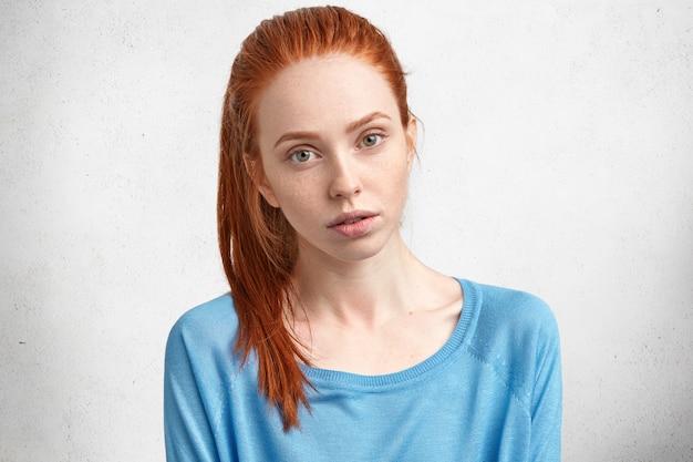 Atrakcyjna rudowłosa modelka o poważnym, pewnym siebie wyrazie, o zdrowej, piegowatej skórze, nosi jasnoniebieski sweter, pozuje na białej betonowej ścianie.