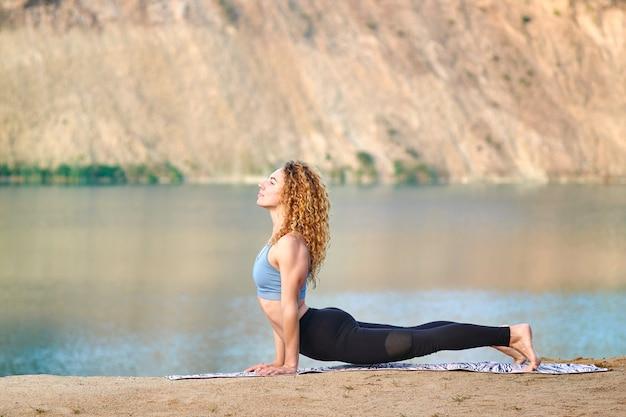 Atrakcyjna rudzielec kędzierzawa kobieta lub model ćwiczy joga outdoors