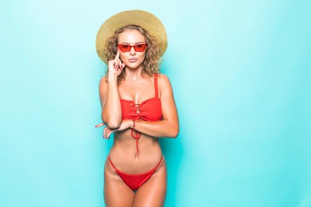 Atrakcyjna seksowna dziewczyna o idealnym ciele w czerwonym bikini, czapce, okularach przeciwsłonecznych, emocjonalnie na niebieskiej ścianie.