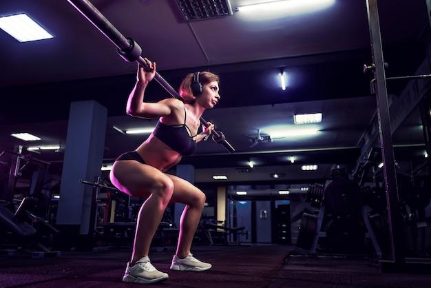 Atrakcyjna seksowna kobieta na siłowni kuca ze sztangą. kobieta szkolenia z powrotem.