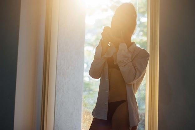 Atrakcyjna seksowna kobieta w gorącej bieliźnie i białej koszuli zapinanej na guziki