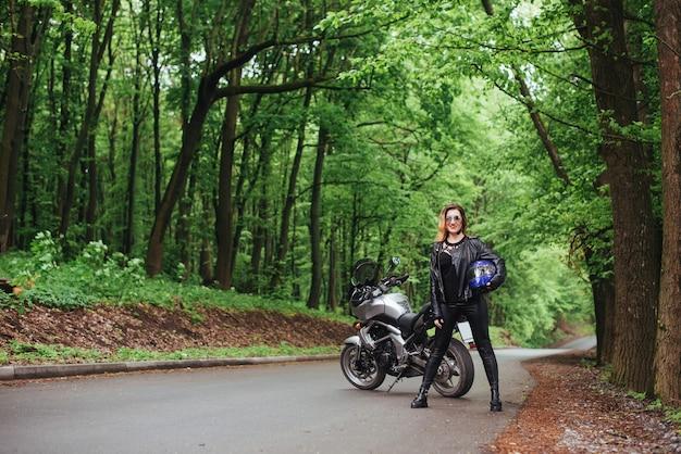 Atrakcyjna sexy dziewczyna ubrana w skórę pozuje w pobliżu motocyklu sportowego na zewnątrz