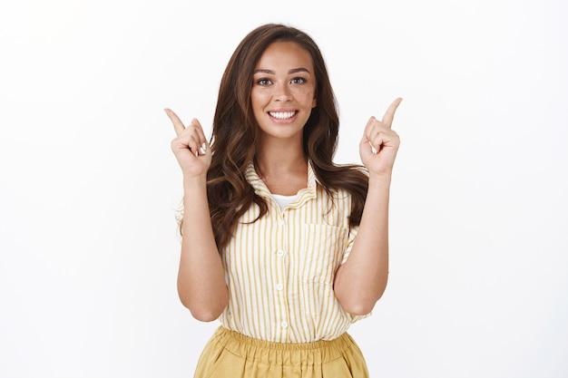Atrakcyjna skromna kaukaska brunetka, uśmiechnięta ząbka i optymistyczna dziewczyna, podnosząca ręce, wskazująca w górę, przedstawiająca dobrą ofertę, proponująca produkt do wypróbowania, wskazująca miejsce na kopię, polecająca świetną obsługę