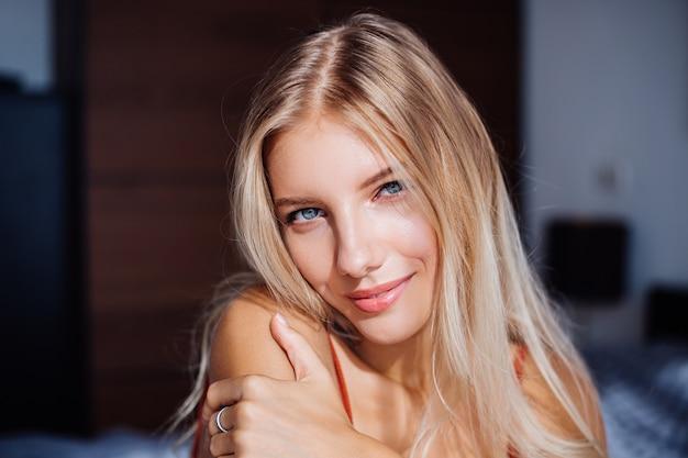 Atrakcyjna śliczna kaukaska europejska kobieta cieszy się pięknym wschodem słońca przy oknie, jest na łóżku w domu